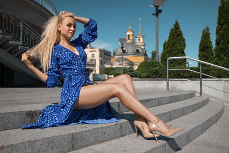 Beautiful blonde girl in the blue dress with perfect legs and shoes with high heels posing outdoor on the city square.