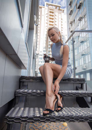 Beautiful blonde girl in grey dress with perfect legs and shoes with high heels posing outdoor at the city square. Street fashion photo. Stock Photo