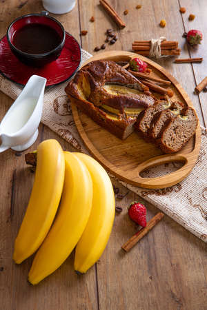 Fresh made hot dessert banana cake on the wooden table with cinnamon, strawberry, and bananas - close-up photo. Stock Photo