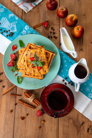 Breakfast with waffles, strawberries, mint and cinnamon on a wooden table in the rays of the morning sun. Reklamní fotografie - 154971025