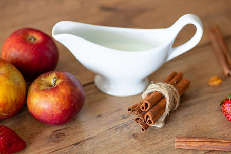 Breakfast table with apples, milk and cinnamon - close up photo