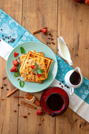 Breakfast with waffles, strawberries, mint and cinnamon on a wooden table in the rays of the morning sun. Reklamní fotografie - 154974070