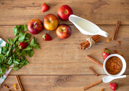 Breakfast table with apples, strawberries, milk, mint and cinnamon - flat lay product photo Stock Photo