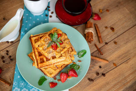 Breakfast with waffles, strawberries, mint and cinnamon on a wooden table in the rays of the morning sun.