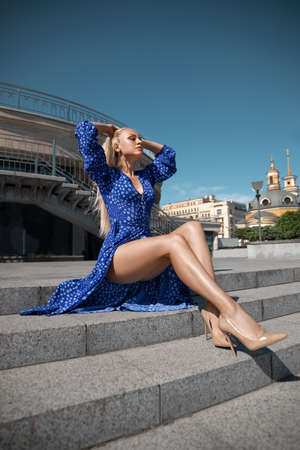 Beautiful blonde girl in the blue dress with perfect legs and shoes with high heels posing outdoor on the city square. Reklamní fotografie - 155483345