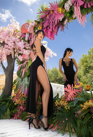 Beautiful brunette girl with perfect shapes in the black dress posing near the pink tree and swimming pool on the white resort. Stock Photo