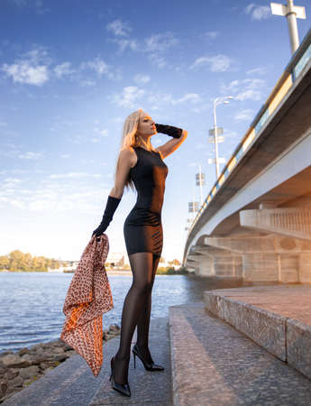 Beautiful blonde girl in black dress with perfect legs in pantyhose and shoes with high heels posing outdoor near the river bridge in the rays of sun-set. Street fashion photo.