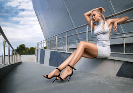 Beautiful blonde girl in grey dress with perfect legs and shoes with high heels posing outdoor at the city square. Street fashion photo. Reklamní fotografie