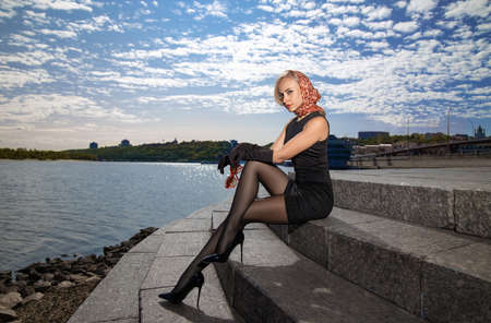 Beautiful blonde girl in black dress with perfect legs in pantyhose and shoes with high heels posing outdoor near the river bridge in the rays of sun. Street fashion photo. Reklamní fotografie