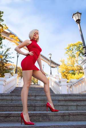 Beautiful blonde girl in the red dress with perfect legs and shoes with high heels posing outdoor in the city park.