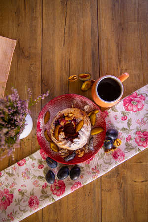 Fresh baked plum cheesecake with coffee cup on the wooden table in the rays of morning sun.