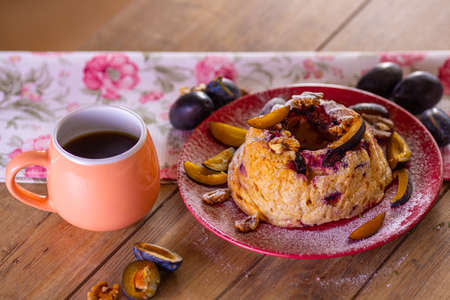 Fresh baked plum cheesecake with coffee cup on the wooden table in the rays of morning sun. Reklamní fotografie - 156414453