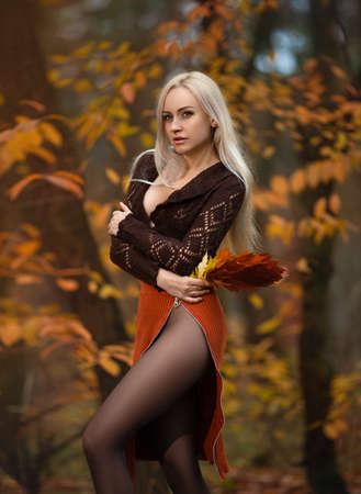 Beautiful woman with perfect legs in pantyhose posing outdoor in the autumn park in the lights of the setting sun.