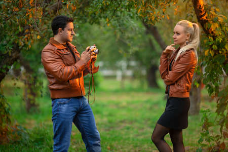 The happy couple, man and woman shooting on the old camera outdoor in the green autumn park in the red bomber leather coats in the rays of the setting sun. Reklamní fotografie