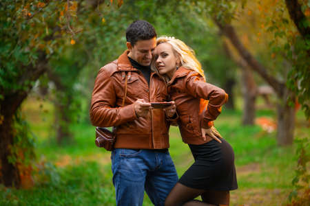 The happy couple, man and woman posing outdoor in the green autumn park in the red bomber leather coats in the rays of the setting sun.