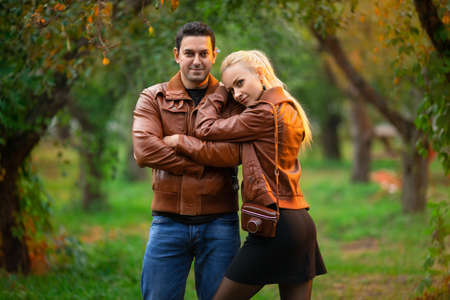 The happy couple, man and woman posing outdoor in the green autumn park in the red bomber leather coats in the rays of the setting sun. Reklamní fotografie - 156870982