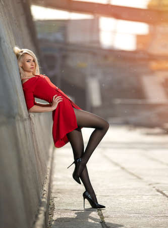 Beautiful blonde woman in red dress with perfect legs in pantyhose posing outdoor at the autumn street in the lights of the setting sun.