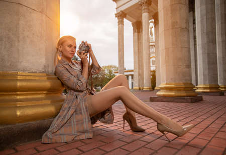 Beautiful blonde girl tourist with perfect legs in stockings shooting with a retro camera outdoor at the old city square in the light of setting sun. Reklamní fotografie - 157502934