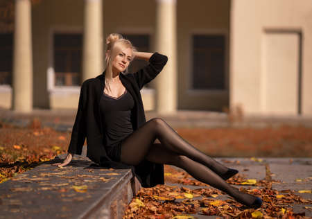 Beautiful blonde woman with perfect legs in pantyhose posing outdoor at the autumn street in the lights of the setting sun. Reklamní fotografie - 157502935