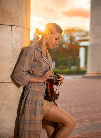 Beautiful blonde girl tourist with perfect legs in stockings shooting with a retro camera outdoor at the old city square in the light of setting sun. Фото со стока