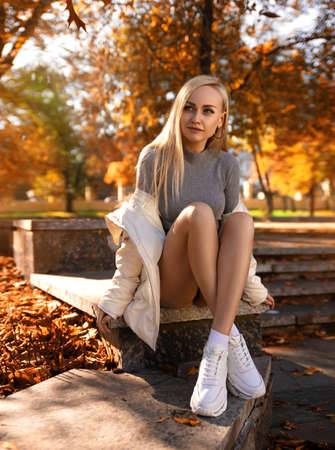 Beautiful student girl with perfect legs sitting on the parapet in the autumn park in white sneakers and coat in the lights of setting sun.