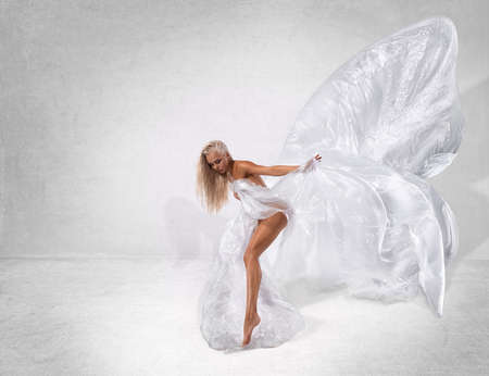 Beautiful sexy fitness girl with great figure posing nude with plastic wings from cellophane bags like a butterfly at the studio. Ecology conceptual photo.