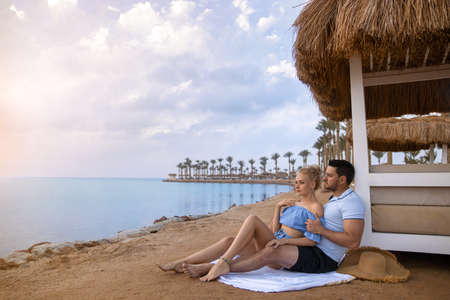 Couple man and woman on the ocean seashore - romantic hugs and sunset at the tropical ocean beach. Happy honeymoon photo. Фото со стока