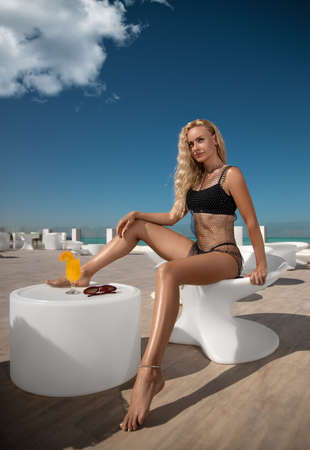 Beautiful woman with perfect legs in black bikini and web posing near the white-colored Santorini resort bar. Wide-angle distortion shoot. Foto de archivo