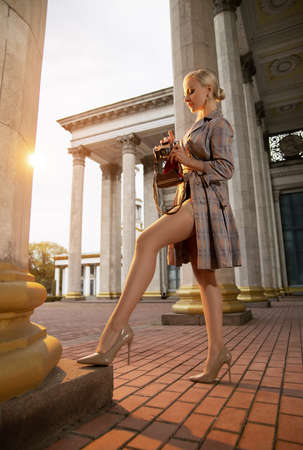 Beautiful blonde girl tourist with perfect legs in stockings shooting with a retro camera outdoor at the old city square in the light of setting sun. Foto de archivo