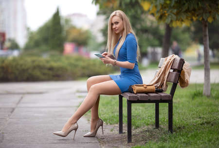 Beautiful blonde girl with phone in a blue dress with perfect legs in pantyhose and shoes with high heels sitting on the bench in the park. Foto de archivo