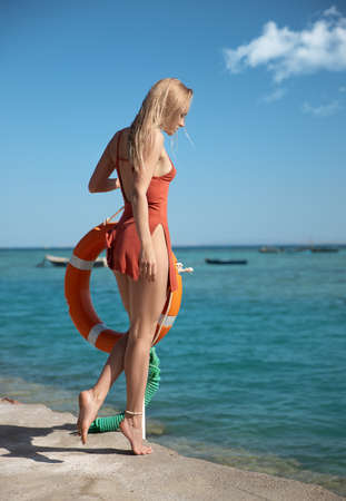 Beautiful woman with perfect legs in red dress posing near Lifebuoy post and watching the sea. Baywatch. Foto de archivo