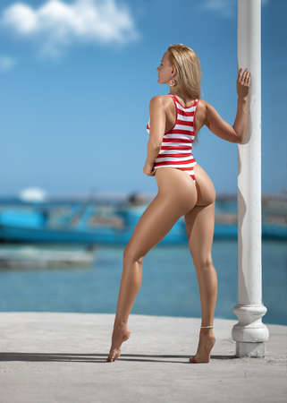 Beautiful fitness woman with perfect butt and legs in red striped swimwear posing on the white-colored Santorini resort shore. Wide-angle distortion shoot.