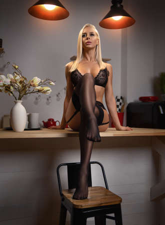 Beautiful blonde girl housewife posing in black lingerie and stockings on the kitchen table - beauty glamour portrait.