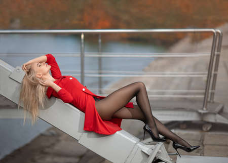Beautiful blonde girl in red dress with perfect legs in pantyhose and shoes with high heels posing outdoor on the city square. Foto de archivo