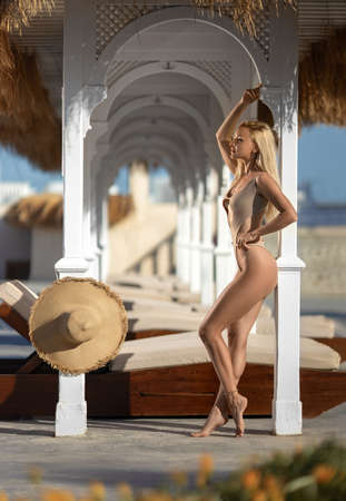 Beautiful woman with perfect legs and large hat posing on the white-colored luxury Santorini resort shore. Foto de archivo