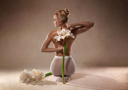Beautiful fitness woman with perfect legs in white fishnet pantyhose and with Amaryllis flowers - fashion style on the studio background.