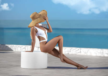 Beautiful fitness woman with perfect butt and legs in white swimwear and large hat posing on the white-colored Santorini resort shore.