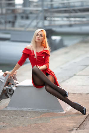 Beautiful blonde girl  with perfect legs in black pantyhose and shoes with high heels posing outdoor on the city square.