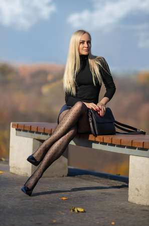 Beautiful blonde woman with perfect legs in pantyhose posing outdoor in the autumn park in the lights of setting sun.
