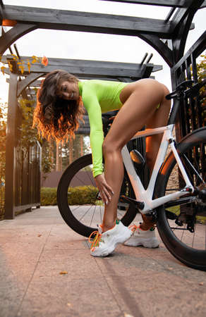 Beautiful fitness girl with a perfect body in swimwear posing outdoor on the bicycle.