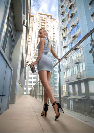 Beautiful blonde girl in grey dress with perfect legs and shoes with high heels posing outdoor at the city square. Street fashion photo. Foto de archivo