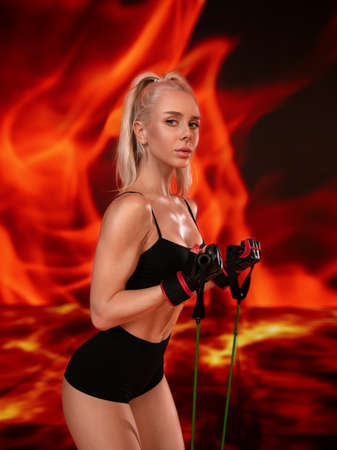 Beautiful blonde fitness girl with ideal shapes posing in black lingerie in the hell fire background.