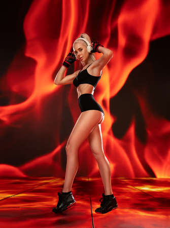 Beautiful blonde fitness girl with ideal shapes posing in black lingerie and earphones in the hell fire background.