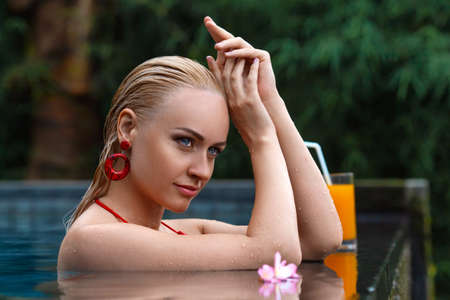 Beautiful blonde woman in swimsuit posing in the tropical swimming pool with glass of juice. Close up beauty portrait. Bali, Ubud. Foto de archivo