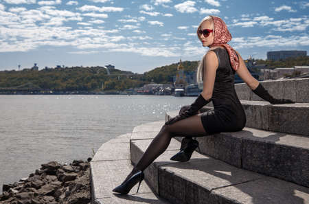 Beautiful blonde girl in black dress with perfect legs in pantyhose and shoes with high heels posing outdoor near the river bridge in the rays of sun. Street fashion photo. Foto de archivo