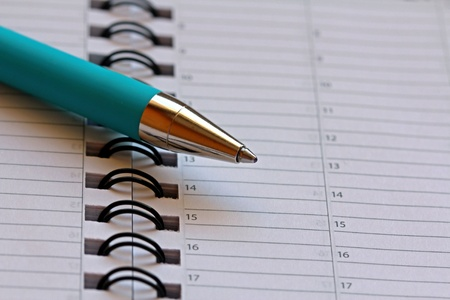 Turquoise ballpoint pen on a weekly calendar page  Space for text, suitable for backgrounds  photo