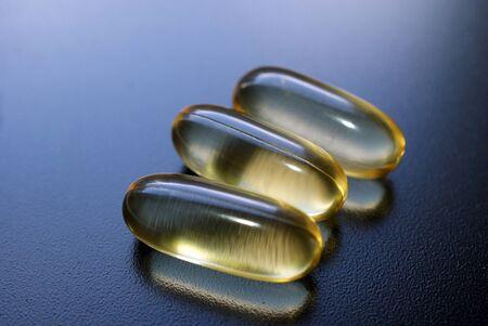 Three fish oil capsules of E-EPA on dark surface   Stock Photo - 13567142