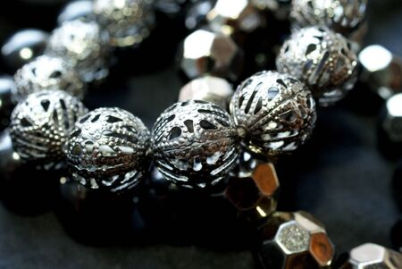 Close up of a bracelet with shiny dark silver beads over black  Soft focus, bokeh effect   photo