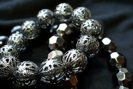 Two bracelets with silver beads over black background, soft focus  photo