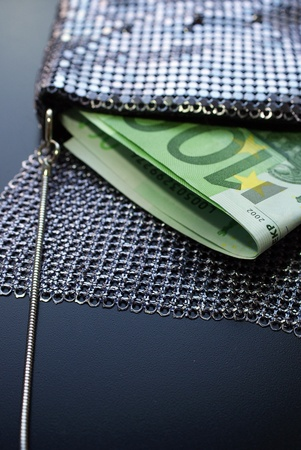 Two hundred Euro bills in a fancy evening bag, vertical view  photo